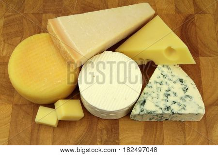 Various cheeses on a kitchen board close up image