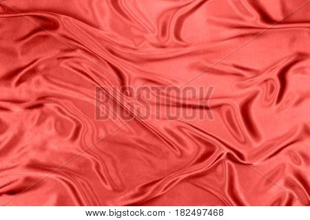 Red wavy silk fabric background close up image