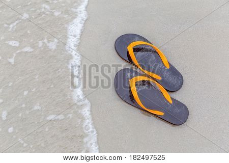 Brown and orange beach slippers soak with motion waving ocean summer vacation concept.