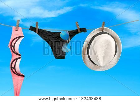 Summer vacation on the beach swimwear and hat on sky background