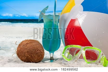 Summer vacation with fresh cocktail on the seaside. Mask goggles and color ball on a sand on beach background