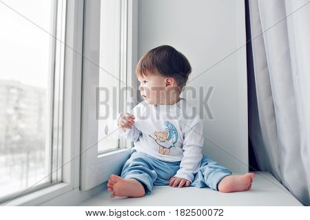 Adorable little baby seating on windowsill. looking out the window.