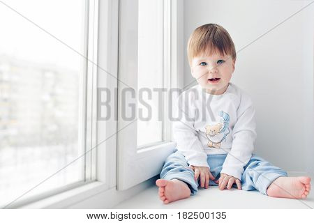 Adorable little baby seating on windowsill. look at the camera.