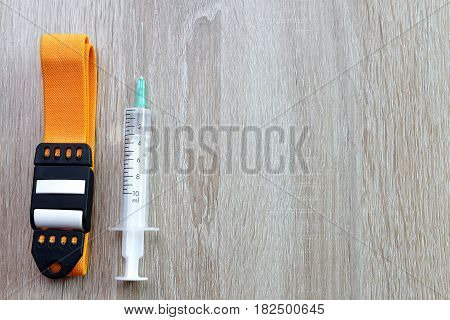 Syringe with tourniquet on the wooden surface.