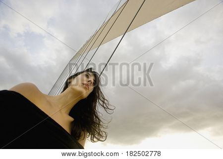 Low angle view of woman with hair blowing outdoors