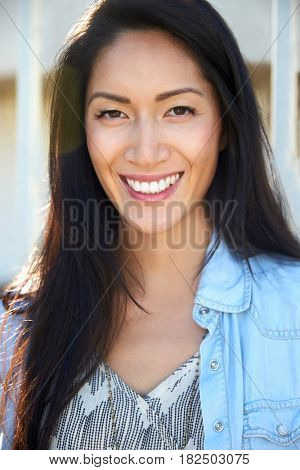 Young mixed race Asian woman smiling outdoors, portrait