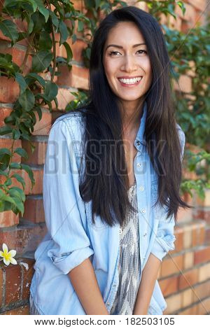 Mixed race Asian woman looking away, three quarter length