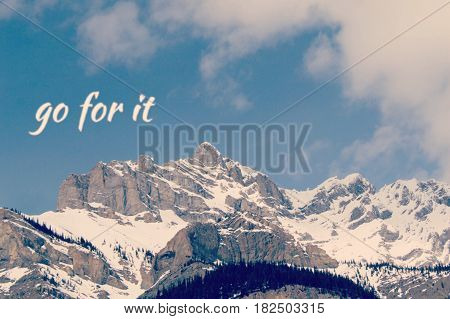 Conceptual mountain landscape view with white text on blue sky over snow covered mountain peaks. Go for it.