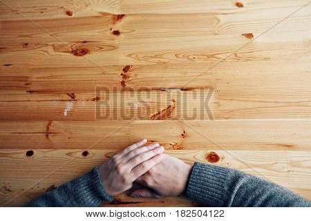 A men hands on a blank wood desk, top view at the studio