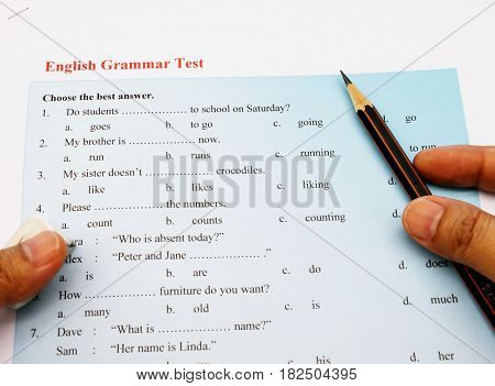 blue english grammar test with hand and pencil