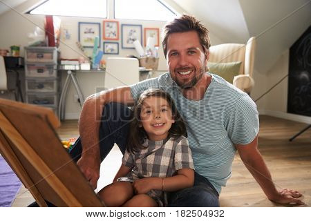 Portrait Of Father And Daughter With Chalkboard In Playroom