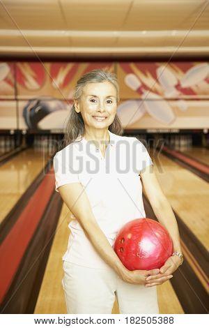 Senior Hispanic woman at bowling alley