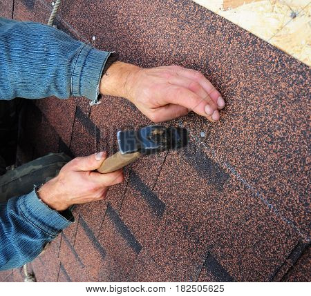 Roofer install  Asphalt Shingles  - closeup on hands. Roof repair and roofing construction.