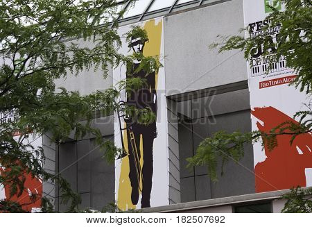 Montreal, Quebec - June 27, 2015 - Wide view of a International Jazz Festival banner on a wall with some tree branches across the foreground in downtown Montreal, Quebec on a bright day at the end of June.