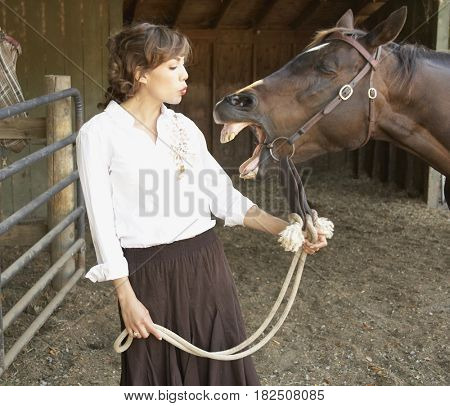 Horse neighing at Hispanic woman in stable