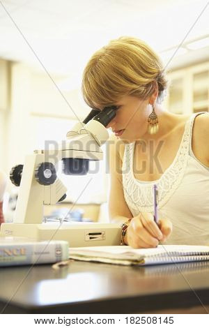 Teenaged girl using microscope in classroom