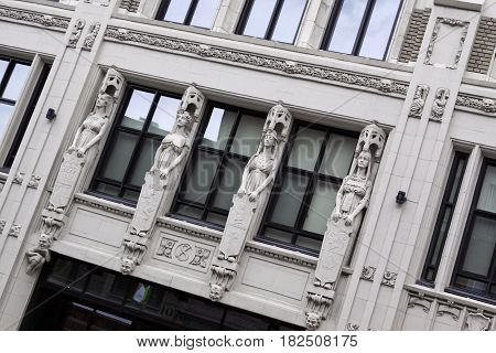 Montreal, Quebec - June 27, 2015 - Wide view of four carved statues on a building in downtown Montreal, Quebec, slightly skewed for dramatic effect, on a bright day at the end of June.
