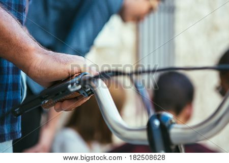 Close up crop shot of hand on bicycle handlebar on background of people talking.