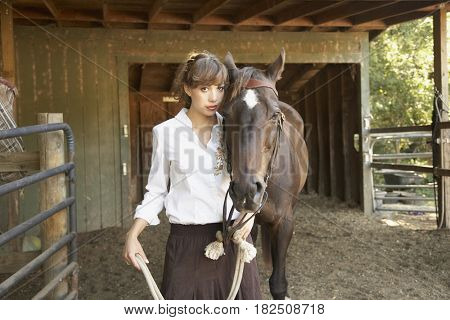Hispanic woman leading horse in stable