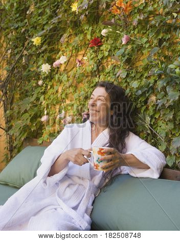 Middle-aged woman in bathrobe drinking coffee outdoors