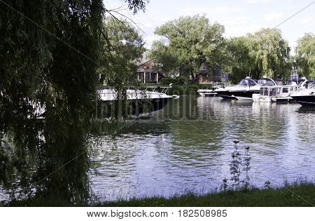 Lachine, Quebec - August 1, 2015 -- Wide view of small yachts docked in the Lachine Canal at Rene Levesque Park, Lachine, Quebec, with the club house and trees in the background on a sunny day in August.