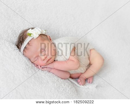 Lovely sleeping baby with a white hairband, dressed in white cute suit napping