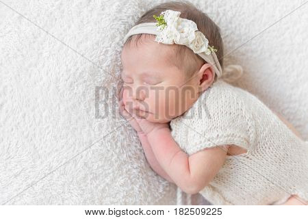 Lovely sleeping baby with a white hairband, dressed in white cute suit napping close-up