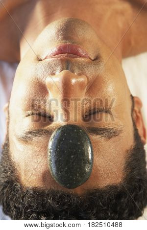 African man receiving stone therapy spa treatment