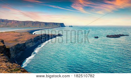 Colorful summer sunset on the Kirkjufjara beach. Evening view of Reynisdrangar cliffs from Dyrholaey peninsula in Atlantic ocean. South Iceland Vic village location Europe. Artistic style post processed photo.