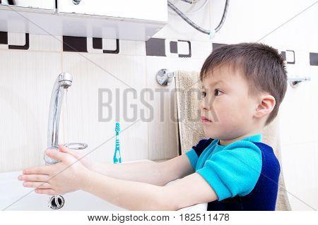 Boy washing hands child personal health care hygiene concept kid washing hand in wash basin in bathroom healthy lifestyle