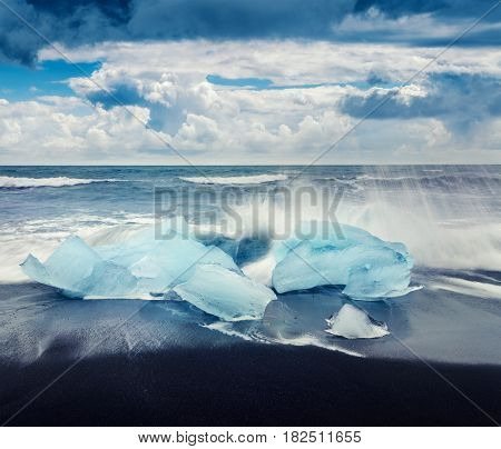 Blocks of ice washed by the waves on Jokulsarlon beach. Dramatic summer morning in Vatnajokull National Park southeast Iceland Europe. Artistic style post processed photo.
