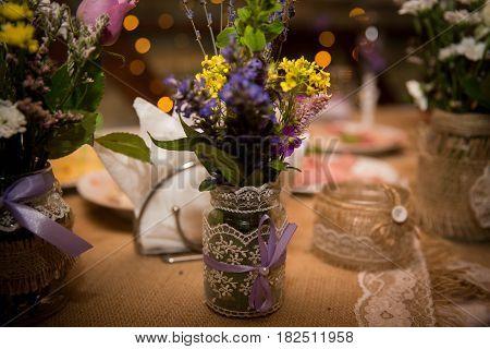 Beautiful bouquet of wild flowers in the designer jar for a wedding celebration. Handmade.