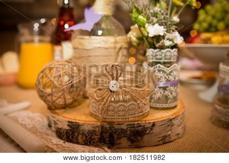 Designer jar decorated with lace and a rope with a button for a wedding celebration. Handmade.