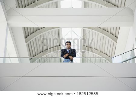 Low angle view of Hispanic businessman on balcony