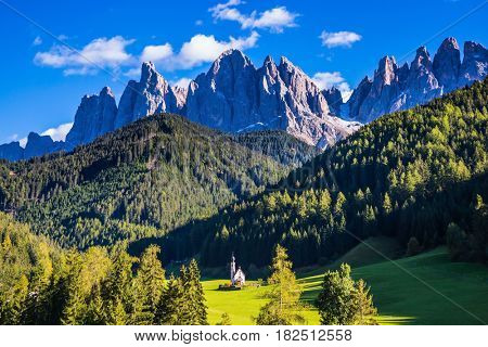 Dolomites, Tirol. Sunny autumn day. Rocky peaks and forested mountains surrounded by green Alpine meadows. The symbol of the valley Val di Funes - church of Santa Maddalena