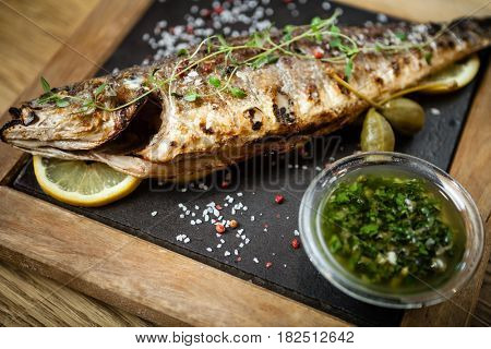Fresh sea bass. Mediterranean fish, baked entirely in a coal stove with herbs and lemon.