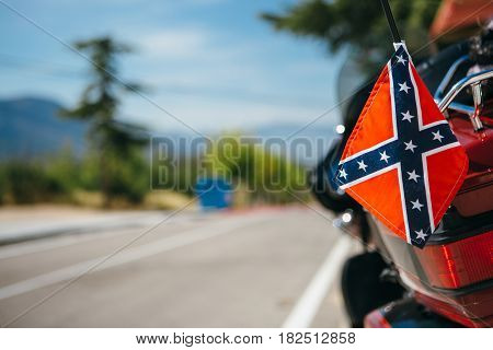 Close up shot of navy flag of Confederacy hanging on bumper of motorbike in sunny day.