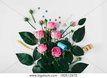 Pink roses with party confetti noise makers and candles on a white background. Colorful celebration background. Flat lay. Top view