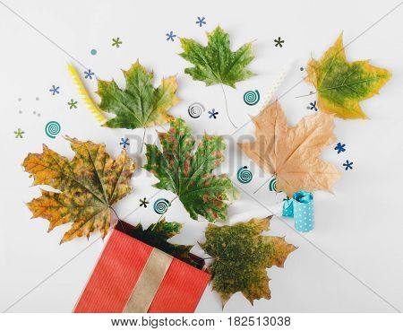 Red gift box with various colorful dry leaves party confetti streamers noise makers and candles on a white background. Colorful celebration background. Flat lay. Top view