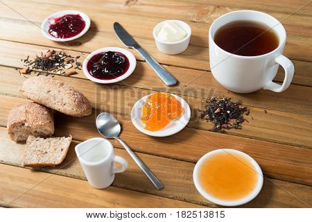 What's your craving for breakfast today. Crispy multi-grain rolls with butter, berry and apple jam - warm and delicious, with black tea for a drink.