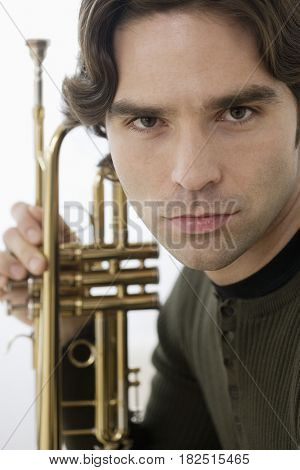 Close up of Hispanic man holding trumpet