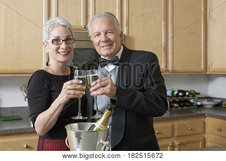 Well dressed senior couple toasting with champagne in kitchen