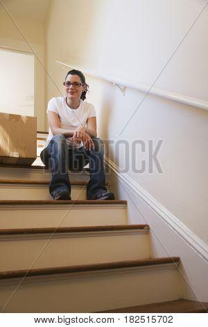 Hispanic woman on stairs next to moving box