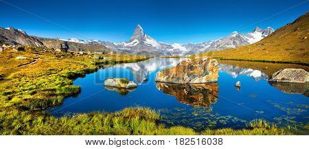 Colorful summer panorama of the Stellisee lake. Reflection of Matterhorn (Monte Cervino Mont Cervin) peak in the watter surface. Beautiful outdoor scene in Swiss Alps Zermatt location Valais canton Switzerland Europe.