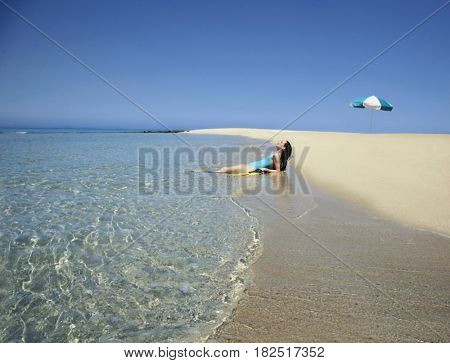 Pacific Islander woman laying in surf at beach