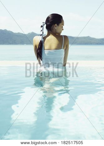 Pacific Islander woman standing in infinity pool