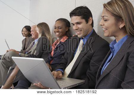 Multi-ethnic businesspeople working on laptops