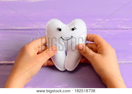 Small child made a felt tooth fairy. Small child holds a cute felt tooth fairy in his hands. Purple wooden background. Simple and fun kids crafts. Closeup