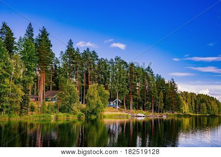 Wooden Log Cabin At The Lake In Summer In Finland