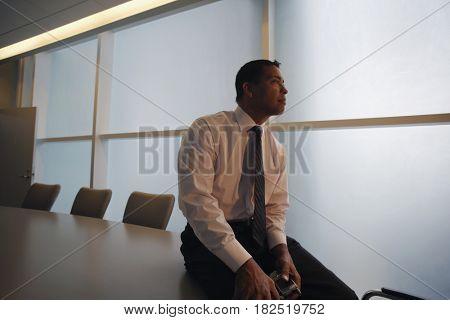 Hispanic businessman sitting on conference table